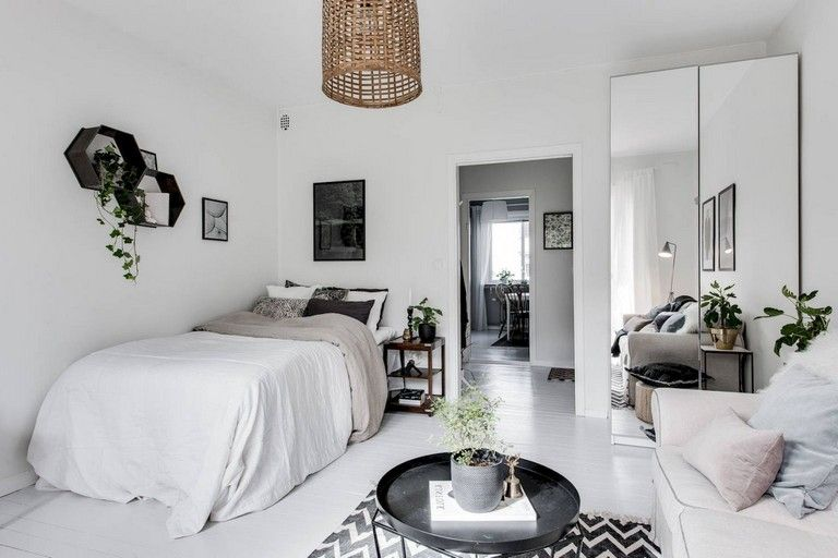 apartment, white floor, white wall, rattan pendant, white sofa, black tray round coffee table, mirror