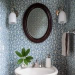 Bathroom, Blue Patterned Wallpaper, White Sink, Round Wooden Mirror, White Sconces