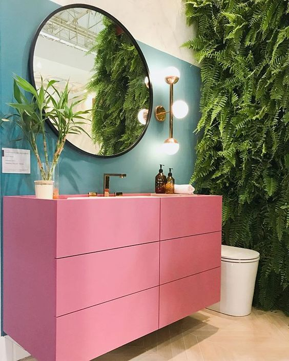 bathroom, brown floor, blue wall, plants on the wall, pink floating cabinet, round mirror