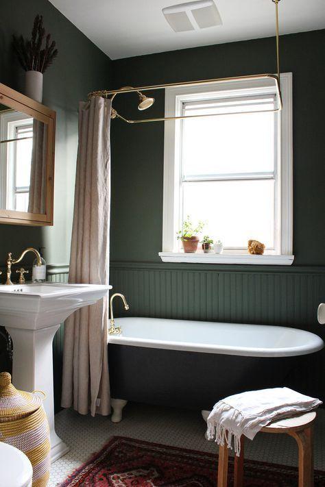 bathroom, dark green wal, white framed window, white sink, dark tub, white floor tiles, patterned ug, wooden chair, white toilet