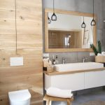 Bathroom, Grey Floor, Wooden Paneled Wall, White Floating Cabinet, Wooden Counter Top, White Sinks, Wooden Stools, White Floating Toilet, Rattan Mat, Grey Wall, Pendants