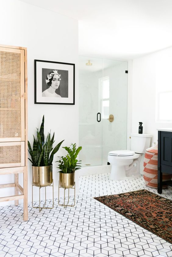 bathroom, hexagonal floor tiles, white wall, white toilet, patterned rug, black cabinet, golden pots, rattan cabinet