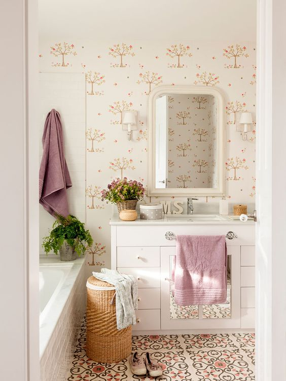 bathroom, patterned floor tiles, patterned wall, white cabinet, mirror, white sconces, white tub