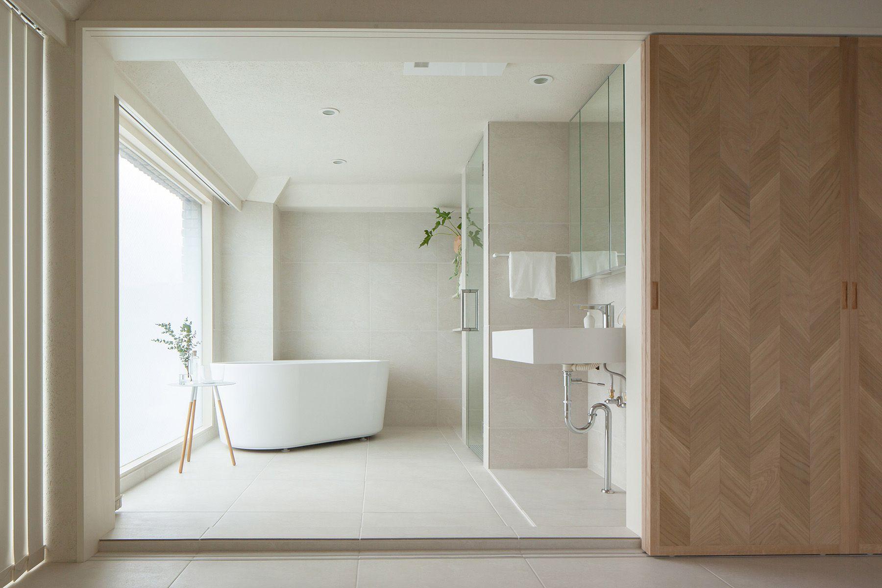 bathroom, white floor tiles, white tub, white side table, sliding door, windows, shower area with glass