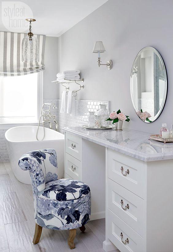 bathroom, white floor tiles, white wall, white cabinet, white tub, flowery chair, white marble top, round mirror, glass chandelier, white sconces