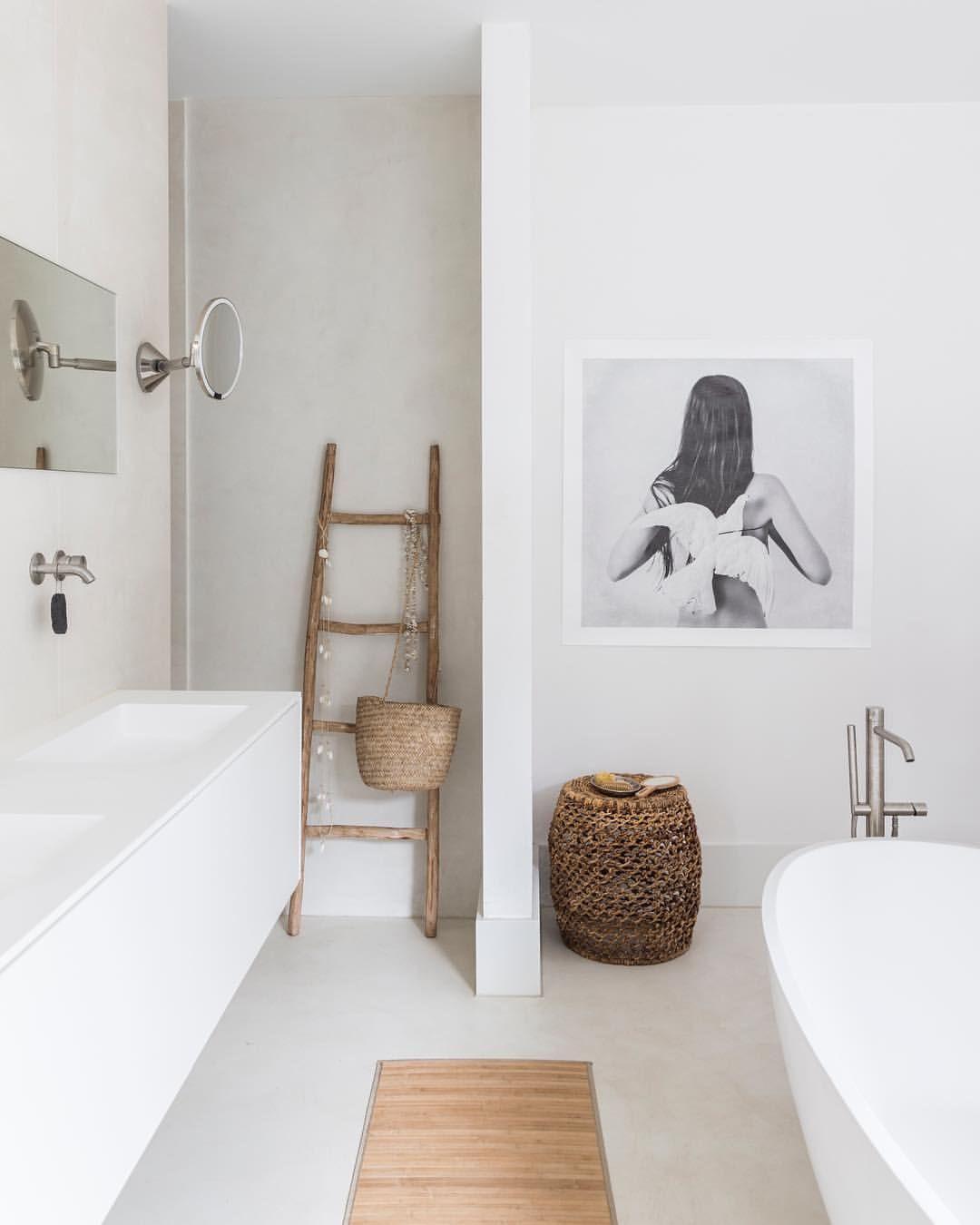 bathroom, white floor, white tub, white wall, white floating vanity, mirror, wooden rack, rattan basket