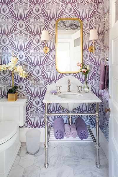 bathroom, white hexagonal marble floor tiles, purple wallpaper, white marble vanity, golden framed mirror, white sconces