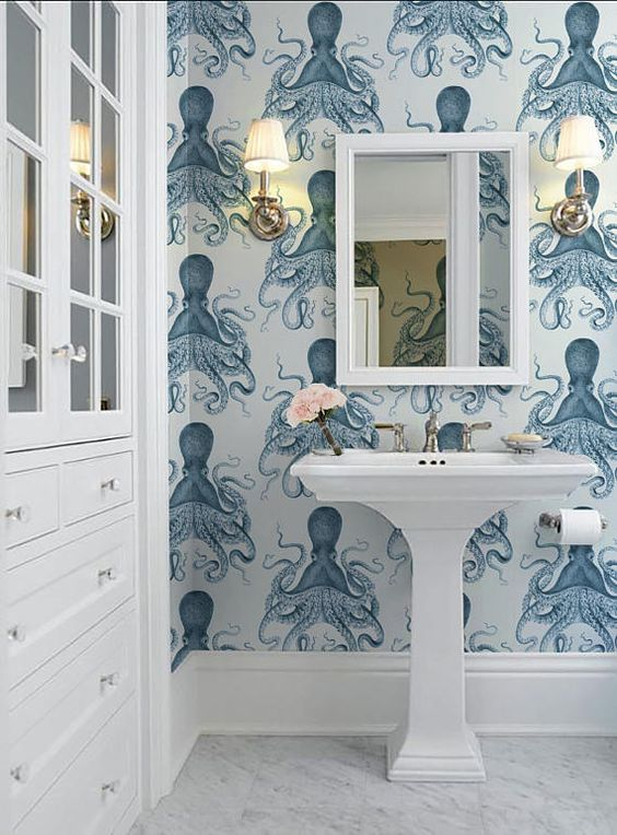 bathroom, white marble floor, white sink, white framed mirror, blue octopus wallpaper, white sconces