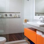 Bathroom, White Tiny Floor Tiles, White Tiny Wall Tiles, Wooden Floor, Grey Vanity Counter, Orange Cabinet