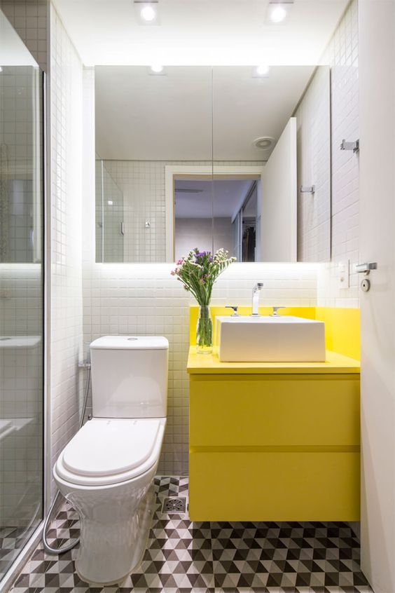 bathroom, white tiny wall tiles, geometrical floor tiles, white toilet, yellow cabinet, white sink