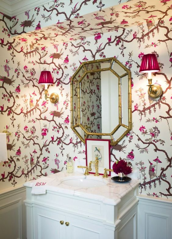 bathroom, white wainscoting, white cabinet, white marble top, golden framed mirror, pink sconces