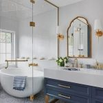 Bathroom, White Wall, Blue Cabinet With White Counter Top, Golden Framed Mirror, White Sconces, White Bowl Tub, Patterned Floor