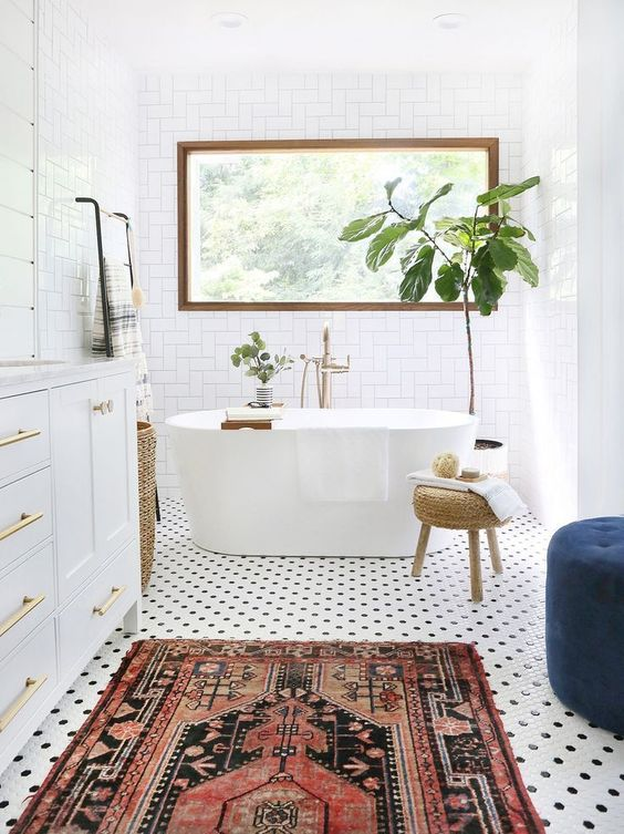 bathroom, white wall floor, white tiny hexagonal floor tiles, patterned rug, white cabinet, rattan stool, blue ottoman