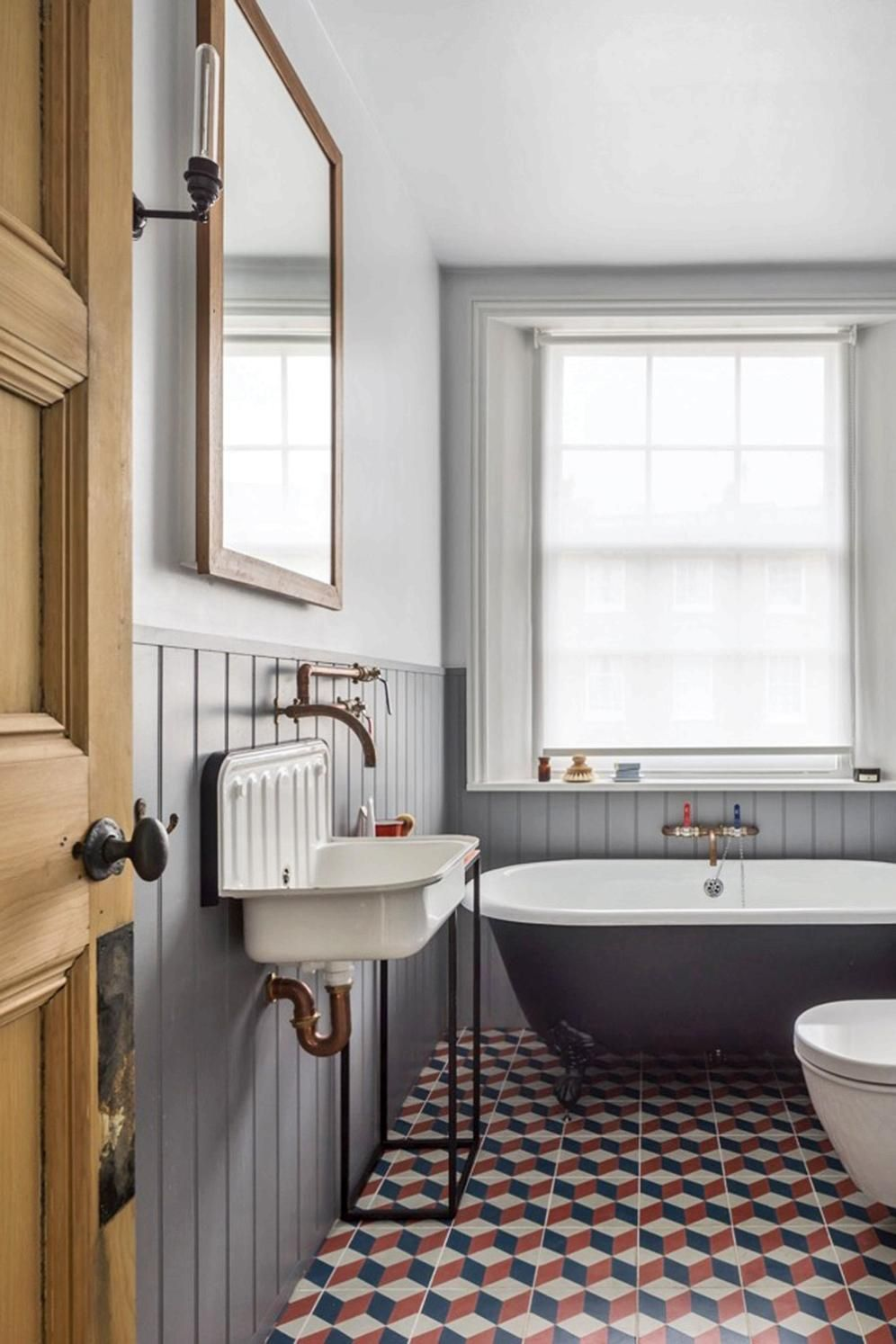 bathroom, white wall, grey wainscoting, black tub, white vintage sink, patterned floor tiles