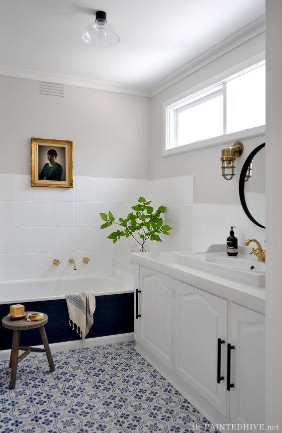 bathroom, white wall, white wall tiles, black tub, white cabinet, white sink, golden faucet, black round mirror