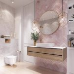 Bathroom, Wooden Floor, White Marble Wall,pink Herringbone Accent Wall, Floating Wooden Vanity, White Top, White Sink, Round Mirror, Pendants