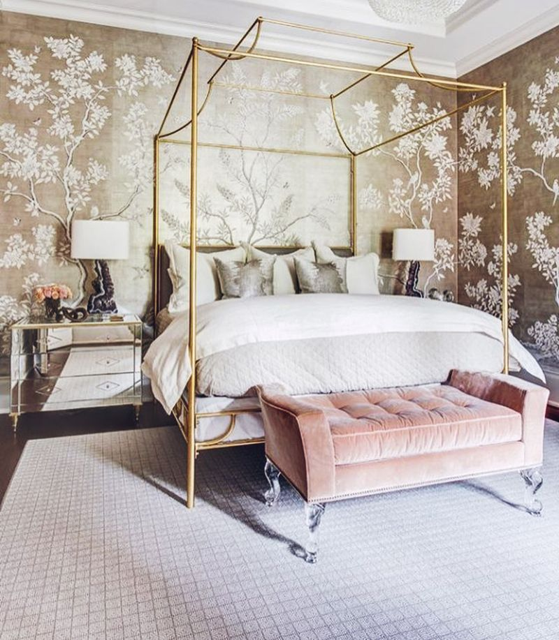 bedroom, black floor, grey rug, golden wallpaper, mirrored side cabinet, white table lamp, golden framed bed platform, pink tufted bench