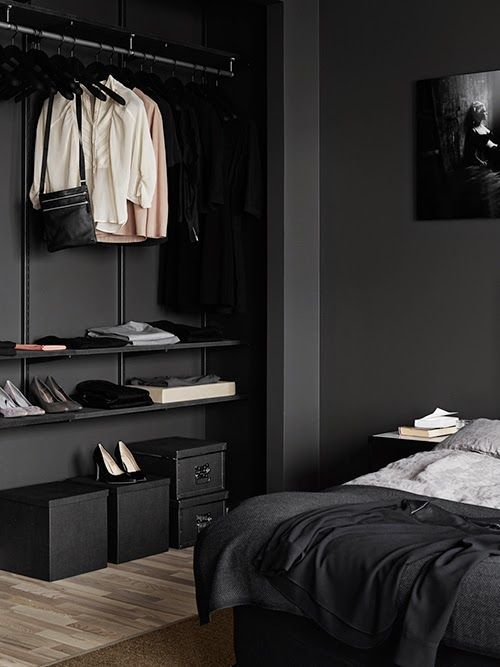 bedroom, black wall, indented walking closet, wooden floor, brown rug, black bedside table, black bedding
