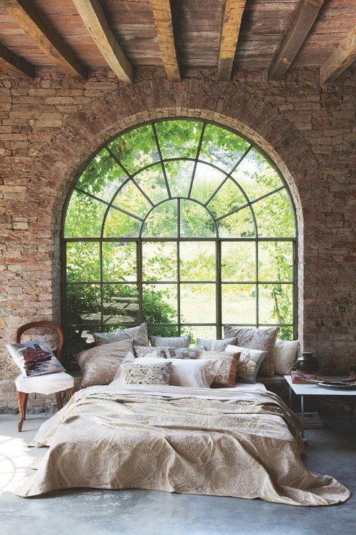bedroom, grey concrete floor, exposed brick wall, glass window, half round glass window, bed, pillows, side table, wooden chair
