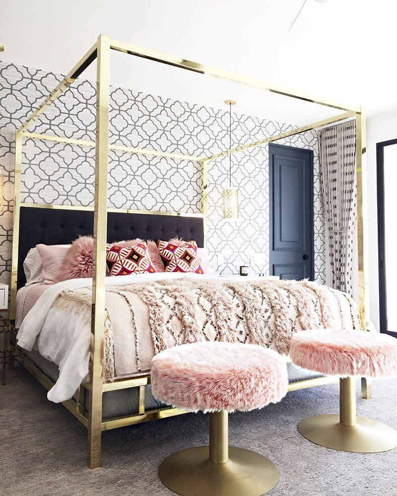 bedroom, grey floor rug, geometrical wallpaper, golden bed platform, pink fur stool, side table, black door