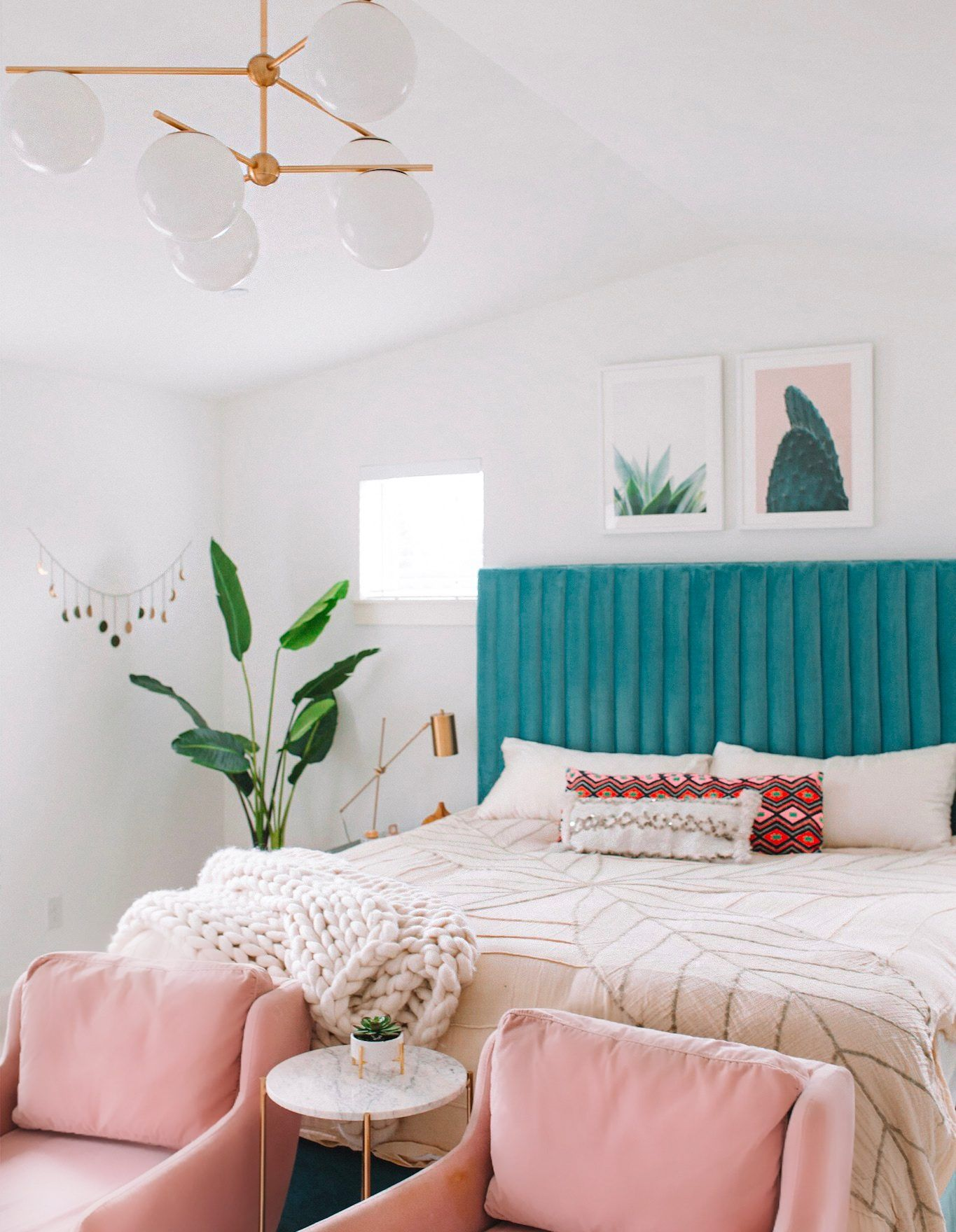 bedroom, white wall, pink chairs, blue velvet headboard, plants, white bulbs chandelier