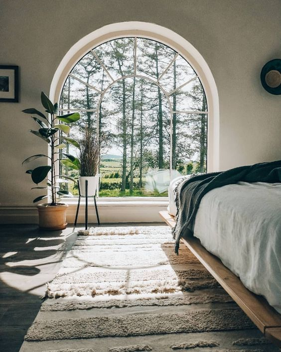 bedroom, white wall, wooden floor, rug, wooden bed platform, half round glass window