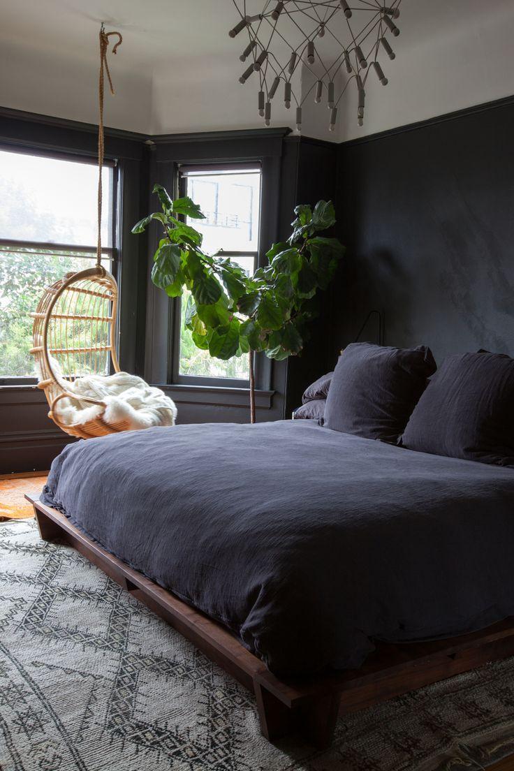 bedroom, wooden floor, black wall, black bedding, wooden bed platform, rattan swing