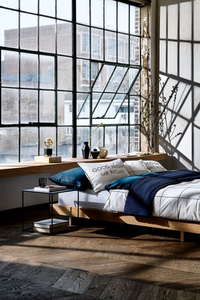 bedroom, wooden floor, concrete wall, glass window, wooden bed platform, black side table, wooden window seat