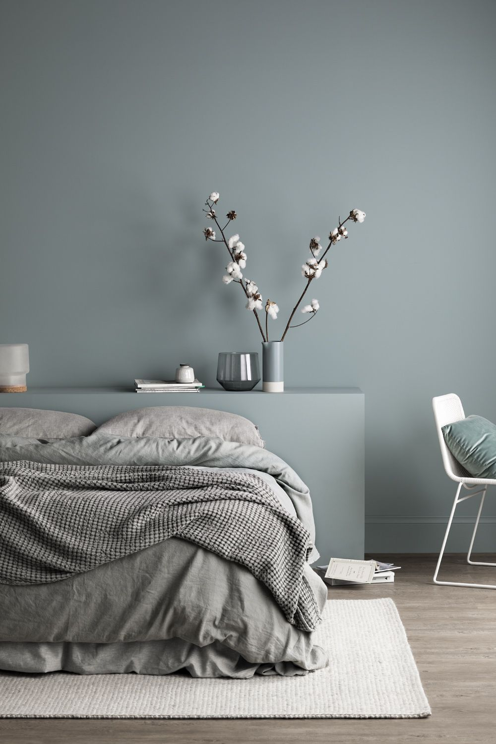 bedroom, wooden floor, light green wall, bed without platform, white chair, white rug
