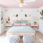 Bedroom, Wooden Floor, White Wallpaper, Pink Ceiling, Whie Ceiling Fan, Wooden Bed Platform, Blue Ottoman, Floating Wooden Side Table, Copper Sconces, Floating Shelves