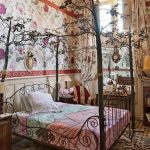 Black Bed Frame With Branches Above, Metal Curve On The Head And Foot, Flowery On The Side, Patterned Floor Tiles, Lion Skin Rug, Flowery Wall, White Wainscoting