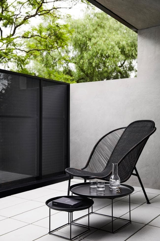 black rattan chair, black tray tables, grey floor, concrete wall, black screen