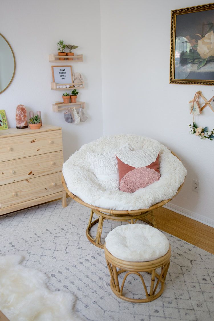 corner, wooden floor, white patterned rug, white wall, wooden cabinet, rattan round chair, rattan ottoman, white cushion, floating shelves