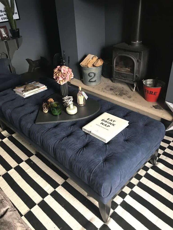 dark blue tufted ottoman, black white striped rug, grey wall, fireplace