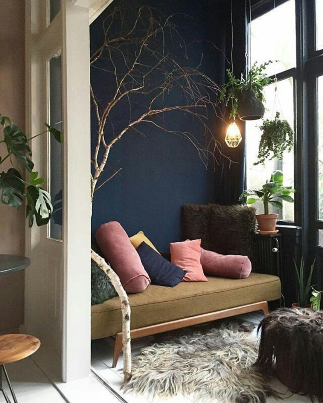 dark blue wall, white floor, brown bench, grey rug, hanging plants pots