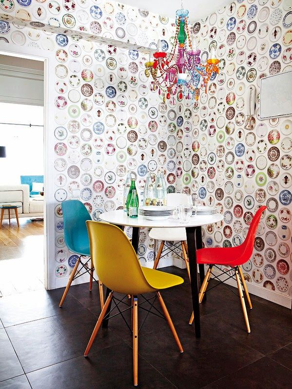 dining room, black floor tiles, blu red yellow modern chairs, white round table, patterned wall, colorful chandelier