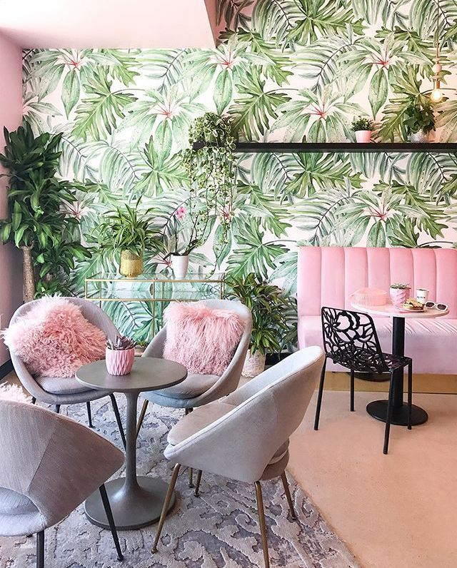 dining room, leaves wallpaper, pink floor, grey modern chairs, pink sofa, black floating shelves