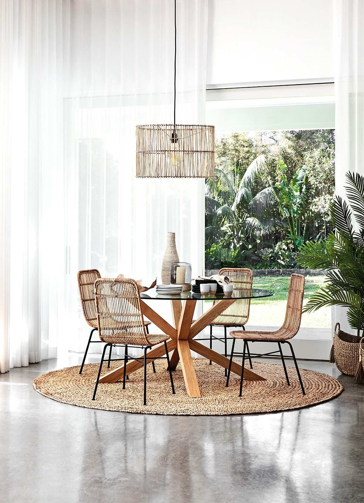 dining room, seamless grey floor, white curtain, glass round table with wooden legs, rattan chairs, rattan pendants
