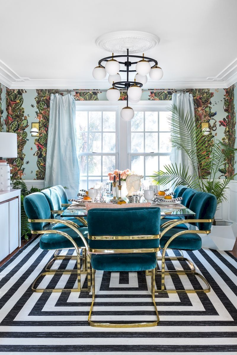 dining room, striped rug, flower wallpaper, blue velvet chairs with golden lines, glass table, white chandelier