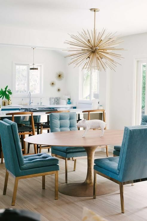 dining room, wooden floor, wooden tulip table, blue tufted leathered chairs with golden legs