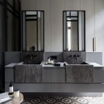 Grey Floating Vanity, Black Marble Sink, Grey Wall, Tall Mirror, Patterned Floor Tiles, Wooden Side Table