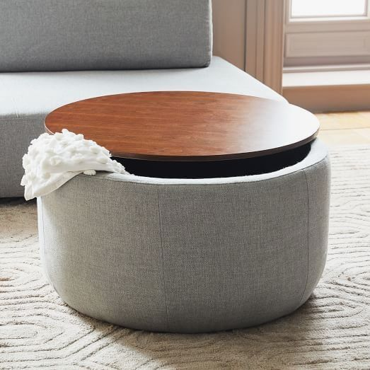 grey smooth ottoman, round wooden top, grey sofa, cream rug