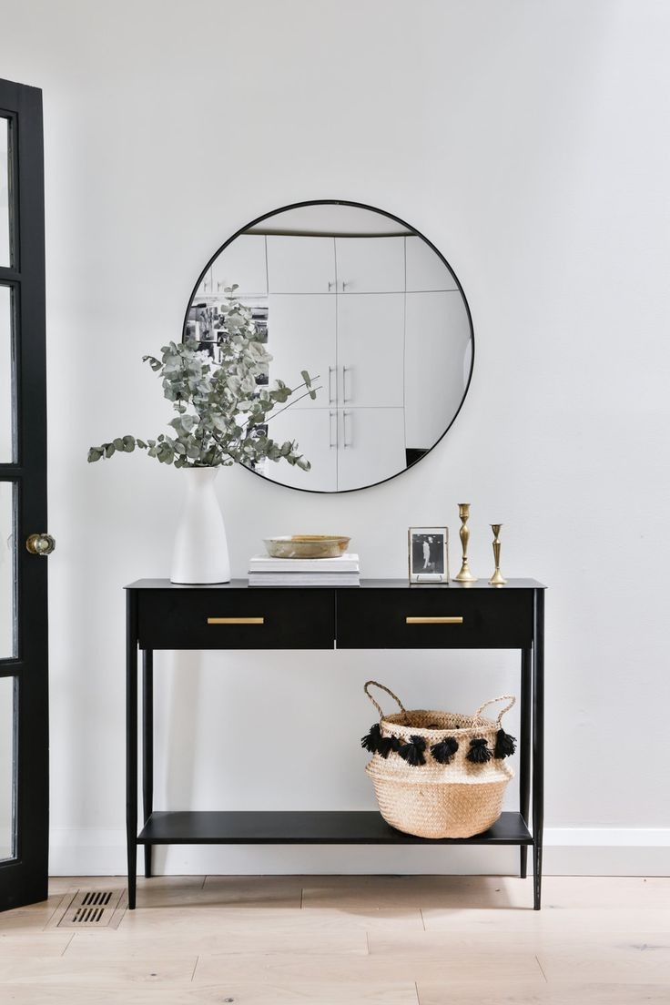 hallway, white wall, black console table with drawers, round mirror, white vase