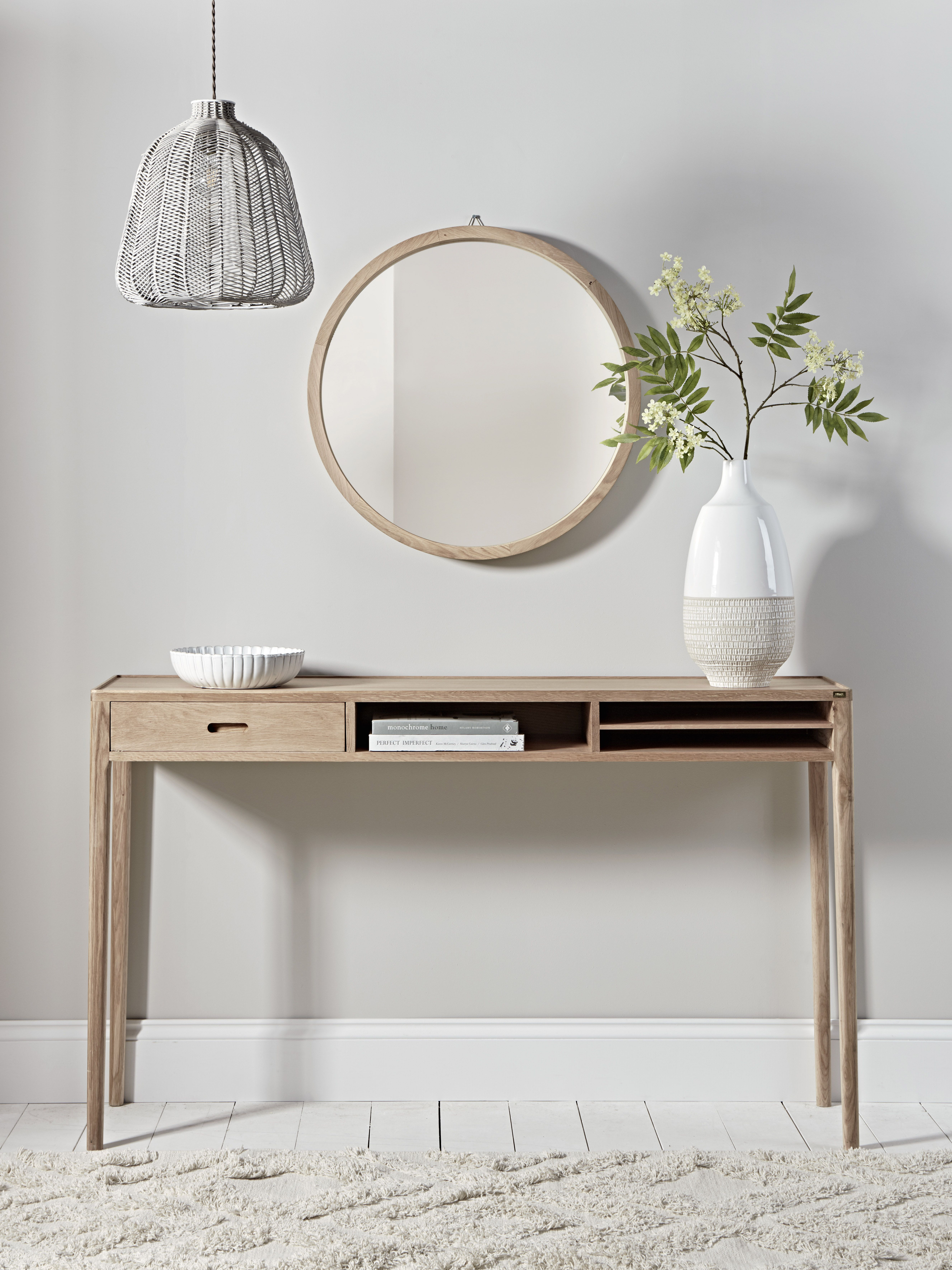 hallway, white wall, white wooden floor, wooden console table with drawers, wooden framed round mirror, pendant, white rug