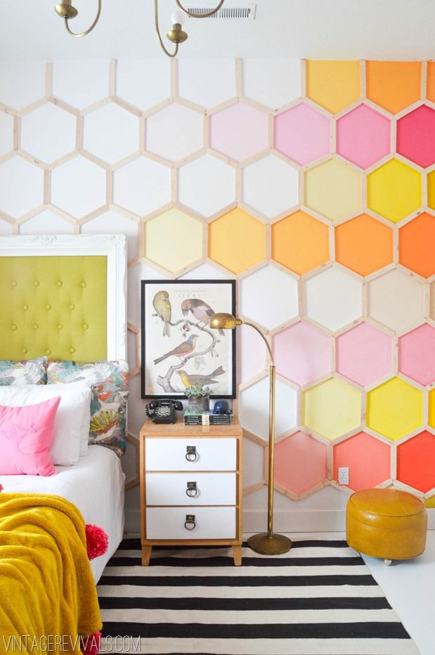 hexagonal accent in white orange, pink, white wall, white floor, white black striped rug, wooden white side cabinet, golden floor lamp