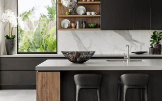 kitchen, seamless grey floor, black island with grey top, white marble backsplash, wooden floating shelves, black upper cabinet, black stools, silver ball pendants