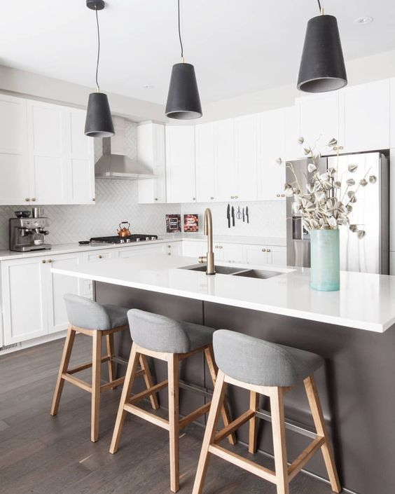 kitchen, wooden floor, white cabinet, grey island, white counter top, black pendant, white backsplash