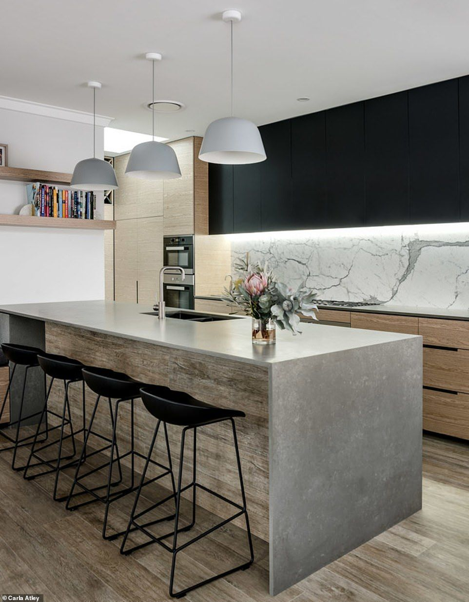 kitchen, wooden floor, white wall, grey counter top, wooden island, wooden cabinet, black upper cabinet, white marble backsplash, white pendants, black stools