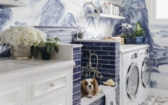 laudry room, painting wallpaper, blue subway tiles, white machines, white wooden shelves, patterned floor tiles, white cabinet