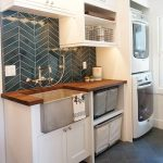Laundry Room, Dark Grey Floor Tiles, White Shelves, White Cabinet, Vertically Stacked White Machines, Dark Grey Backsplash, Wooden Counter Top, Grey Apron Sink